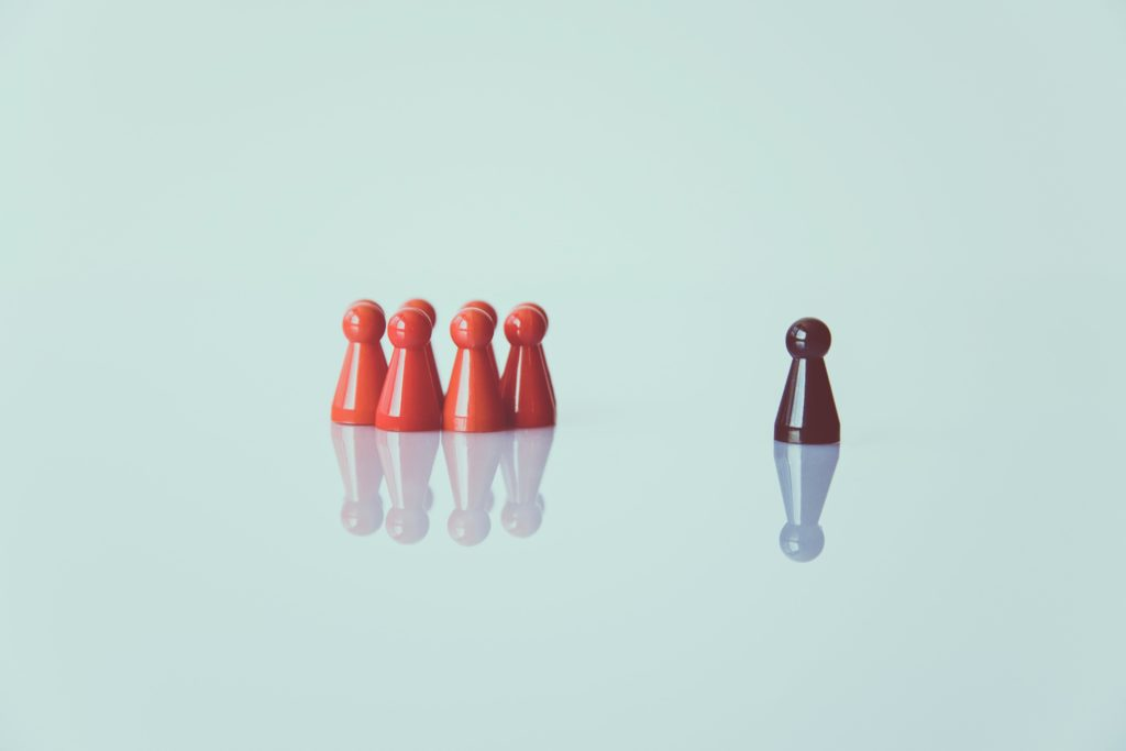 Picture of some little orange people figures standing separate to a brown little person figure.